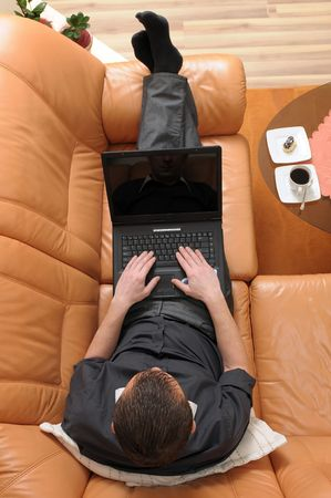 Top view of businessman laying on luxurious leather sofa and working on portable computer. photo