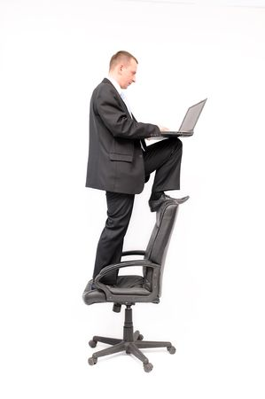 Businessman standing on the black chair and working on the portable computer. Isolated on the white background. photo