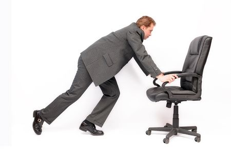 designer chair: Young businessman pushing swivel chair on the career path.