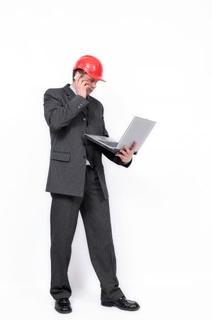 Elegant architect in red helmet standing with open laptop and talking by mobile phone. Isolated on a white background. photo