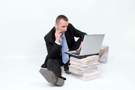 Young businessman on phone, sitting on the floor with laptop on the heap of documents. Isolated on the white background. photo