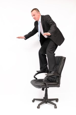 arm chairs: Businessman standing on a chair trying to keep his balance. Stock Photo