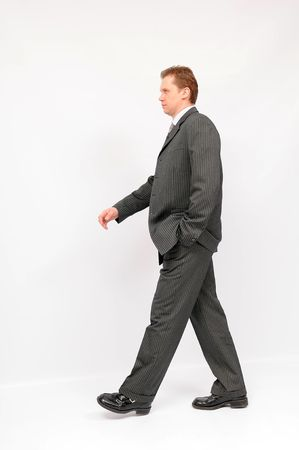 executive assistants: Young walking businessman, isolated on a white background. Stock Photo