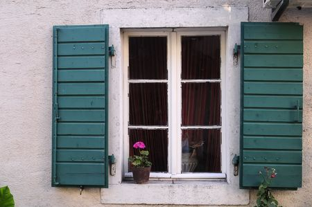 Closeup of the old window with flower and green shutters. photo