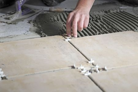 A construction worker putting tiles on the floor. photo