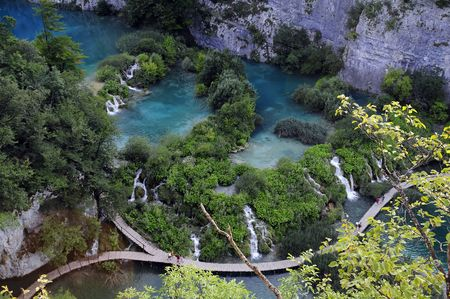 Beautiful top view of wooden path thru Plitvice lakes in Croatia, along soft waterfalls. photo