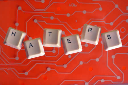 Keyboard keys form the word HATERS on orange electric circuit in the background.