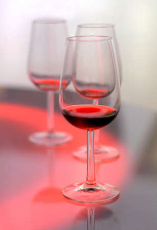 Three glasses of red wine on bright color background