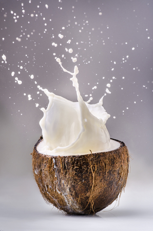 milk poured into a half of coconut that generates a big splash