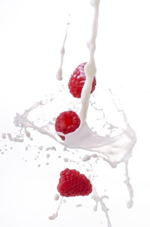 energetic splash of fresh milk on top of raspberries on white background Imagens