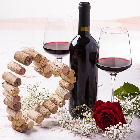 romantic dinner with red wine, floral decoration and silhouette of a heart built with corks