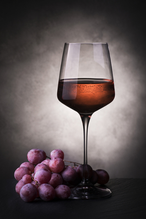 still life with glass of rose wine and bunch of grapes Imagens