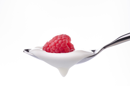 a spoon filled with yogurt with a whole fresh raspberry over it on a white background