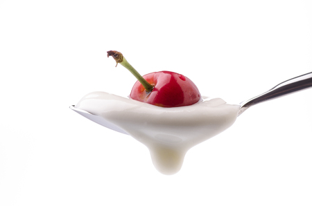 a spoon filled with yogurt with a whole red cherry on top on a white background