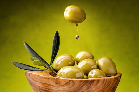 groene olijven met druppel olijfolie vallen in een houten kom vol met olijven Stockfoto