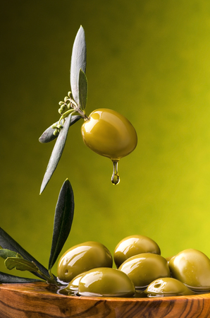 extra virgin olive oil flows on a wooden bowl full of green olives