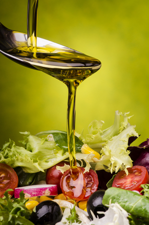 fresh mixed salad topped with a drizzle of olive oil on a green background 写真素材