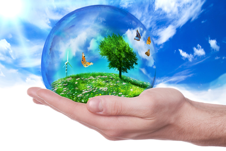 hand holding a planet represented by a green nature and a serene environment and ecological