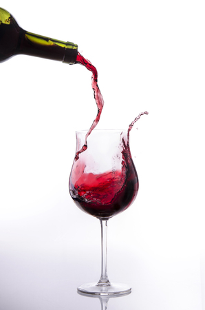 Red wine poured into a glass goblet generates a splash Banco de Imagens