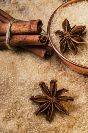 Background of raw cane sugar with star anise and cinnamon sticks Banco de Imagens