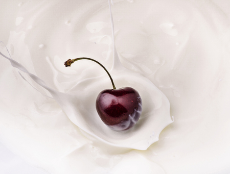 a beautiful cherry falls into the bowl of fresh yogurt with splash