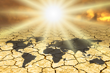 conceptual scene: in a dry environment burned by a dazzling sun, on the arid and cracked land from drought the map of the earth