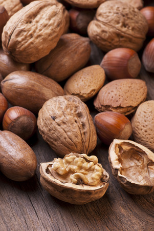 closeup of different types of dried fruit including pecans, almonds and hazelnuts in shell on rustic wooden table Reklamní fotografie