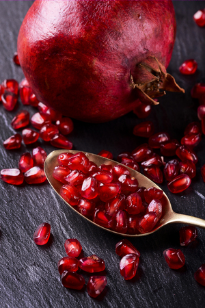 part of some pomegranates on a black slate stone and a spoon contains ripe grains from the scarlet color