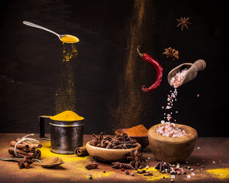 vibrant still life with a wide range of spices with different colors and flavors on the dark background