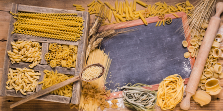 vast assortment of Italian pasta with different sizes and qualities in rustic wooden compartments.space for text Imagens