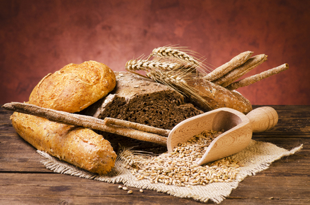 still life, a wide assortment of bread of different types and shapes on the rustic wooden table