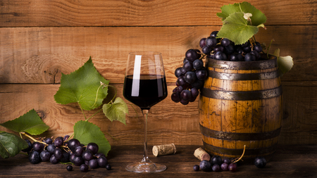 composition with goblet of red wine, grapes with green leaves and wood barrels.still life Reklamní fotografie