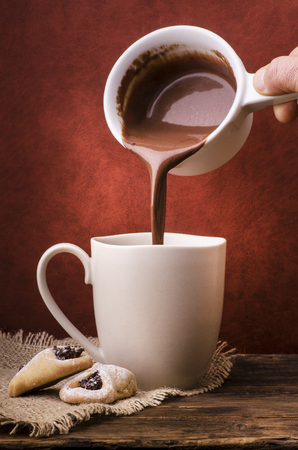 thick and hot chocolate is poured into a white ceramic cup