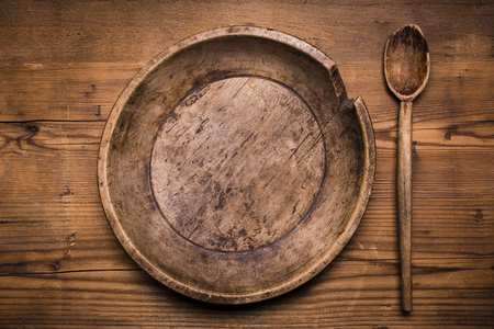 top view of a plate and a vintage wooden spoon on rustic wooden table