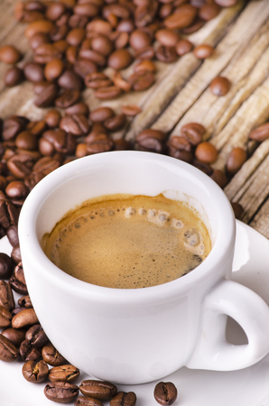 closeup of a cup of hot coffee and roasted coffee beans on rustic wooden table