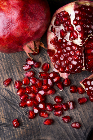 first floor of a ripe pomegranate and juicy, ginned on the rough wooden table