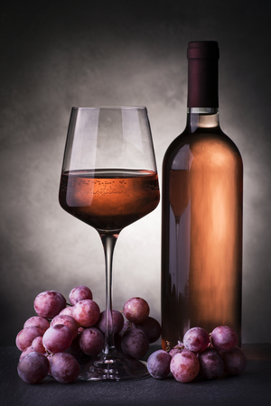 still life. Wine bottle and a glass with rose wine and grapes on the table with dark background Reklamní fotografie