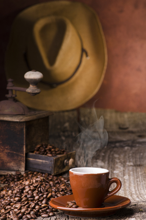 cup of brown color with steaming coffee, in the background a wooden coffee grinder and a brown hat.still lif