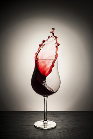 still life. Glass of red wine with sketch, isolated from the dark background. Reklamní fotografie