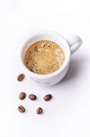 close-up of a small cup of hot coffee with froth and toasted coffee beans on a white background