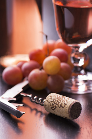 closeup of a corkscrew with cork, in the background a goblet of wine and bunch of red grapes Reklamní fotografie