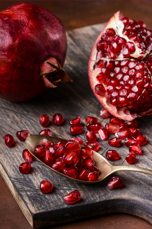part of some pomegranates on a wooden board and a spoon contains ripe grains from the scarlet color Reklamní fotografie
