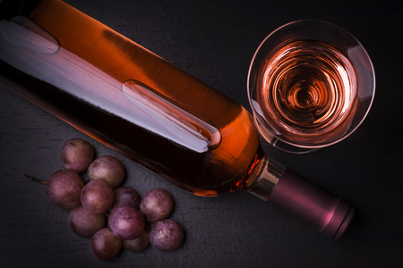 view from above bottle of wine with a glass of wine and grapes pink on dark table Reklamní fotografie