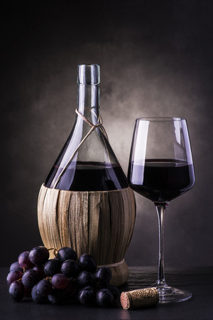 still life .flask of wine and a glass with red wine and grapes on the table with dark background Reklamní fotografie