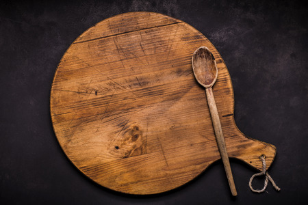 top view of an empty rustic wooden cutting board with spoon on the dark background