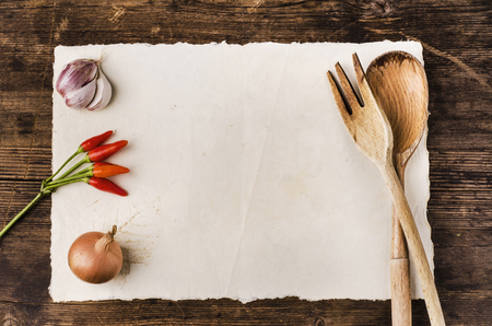 still life. Top view of a white parchment with space for text, wooden utensils and ingredients. Cookbook