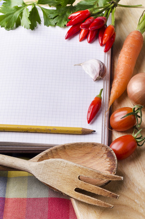 vegetarian diet with fresh vegetables and spices on the old wooden table with empty space for text on the notebook
