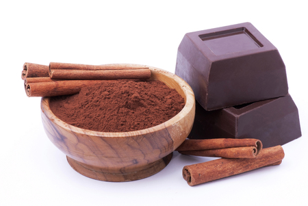 closeup of some pieces of dark chocolate, cocoa powder and cinnamon sticks isolated from the white background