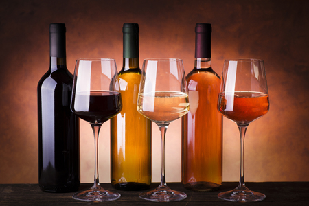 types of wine in bottles and glasses, red, white and rosé wine on rustic wooden table Reklamní fotografie