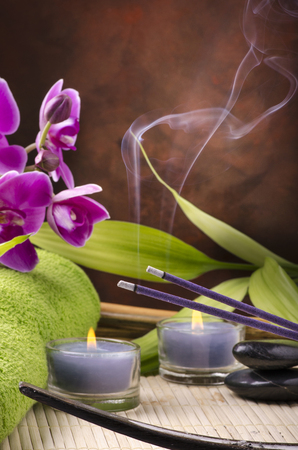 Wellness environment with candles and incense sticks flavored with lavender in the foreground